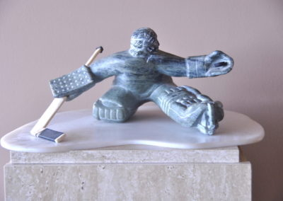 1974 Goalie. Soapstone, Cow Bone, Tape, Rubber Puck with Nylon Base. 14cm high
